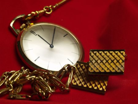 cuff links: gold pocket watch, necklace and cuff links on red velvet