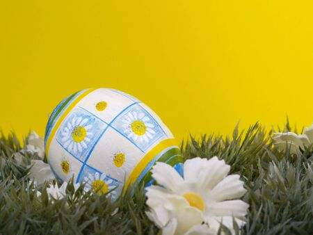 dacorated: handpainted daisy design on easter egg, artificial grass and blossoms, yellow background Stock Photo