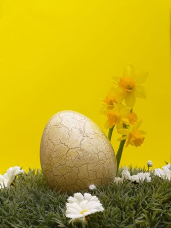 easter egg with drarf daffodils on artificial grass and blossoms, yellow background Stock Photo - 4408131