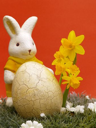 easter egg and bunny with dwarf daffodils on artificial grass and blossoms, red background Stock Photo - 4408182