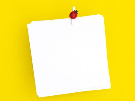 blank white note pad over yellow background