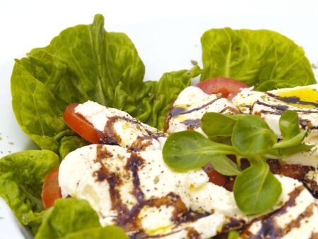 green salad with tomatoes and mozarella cheese, olive oil and balsamico on white plate