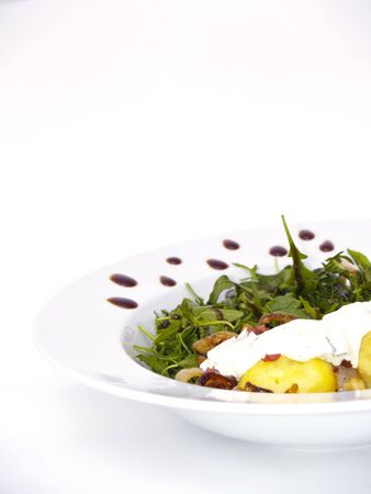 arugola: herbs-flavoured curd and bacon on potatoes with arugola Stock Photo