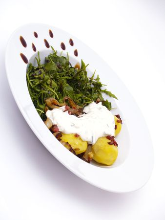 herbs-flavoured curd and bacon on potatoes with arugola Stock Photo