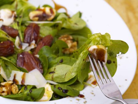 lambs lettuce with dates, walnuts, champignos and parmesan cheese photo