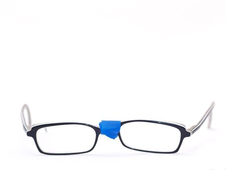 broken eyeglasses provisorily repaired with blue tape Stock Photo