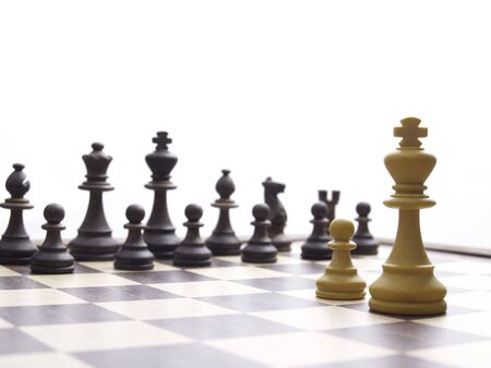 lonely white king and pawn facing black chessmen on chess board, white chessmen in focus
