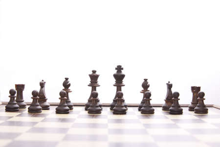 black chessmen on chess board in the beginning of game Stock Photo