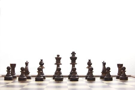 black chessmen on chess board in the beginning of game photo