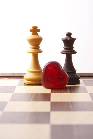white king and black queen on chessboard with heart