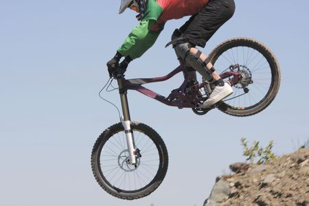 Mountainbiker in downhill race jumping