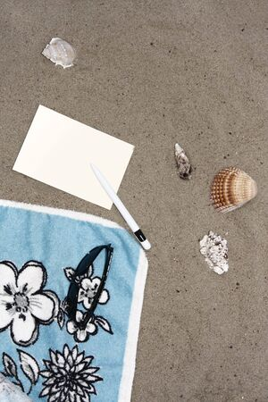 beach towel in the sand with empty postcard and seashells Stock Photo