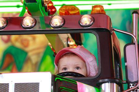 occhi sbarrati: bambina con gli occhi ben aperti al volante di un camion sul carosello Archivio Fotografico