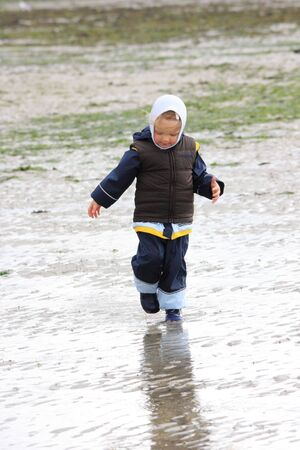 german north sea region: little girl walking on mudland, german north sea region