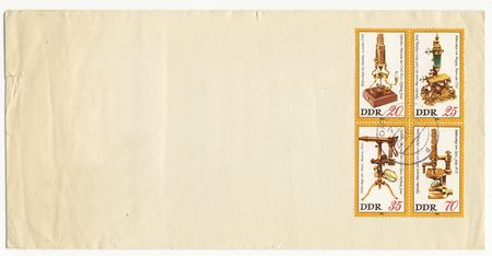 optical equipment: GERMAN DEMOCRATIC REPUBLIC - CIRCA 1980:vintage grungy envelope with optical equipment on old canceled postage stamps Stock Photo