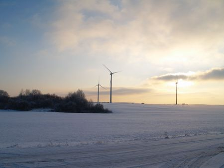 rural german winter landscape with wind turbines and evening sky Stock Photo