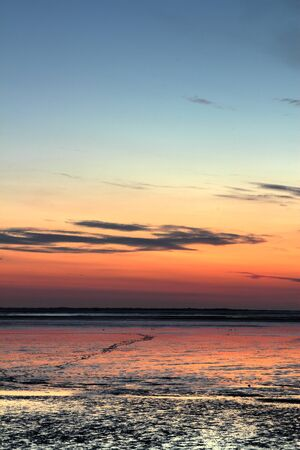 wadden: sun going down over mudflat at the german north sea coast