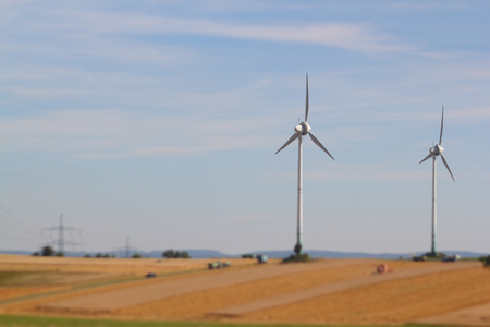 harvesting a barley field  with two wind turbines nearby, focus on wind turbine