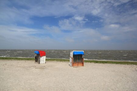 empty beach chairs on a sunny but cool day at the german north sea coast