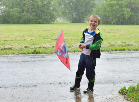 steadfast: Boy squinting to see through rain and not using umbrella