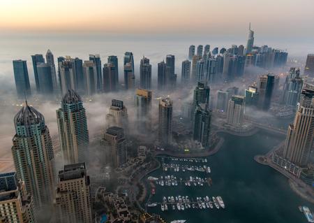sunrise aerial view skyscraper foggy weather Dubai Marina at United Arab Emirates UAE 新闻类图片