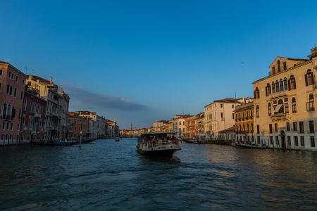 Buildings and traditional Venice gondolas riding on canal in Venice Italy at sunny summer day Stok Fotoğraf