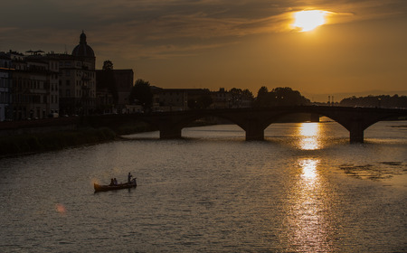 A view of Ponte Vecchio bridge on sunset time and Arno river in Florence. Tuscany, Italy