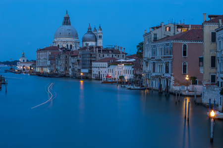Venice city scene with Canal Grande, traditional gondolas and Basilica di Santa Maria della Salute at sunset time Venice Italy
