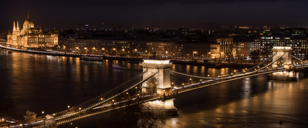 BUDAPEST, HUNGARY - JANUARY 17, 2019 : A view of Chain Bridge on Danube river and Parliament building at night 新闻类图片
