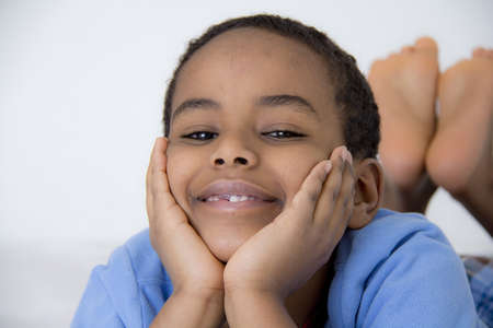 leisureliness: A young boy resting comfortably with his face resting on his hands