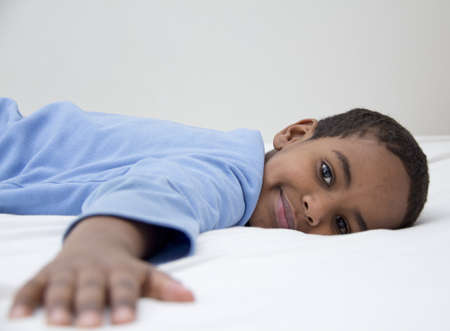 leisureliness: A young african boy resting confortably on his bed