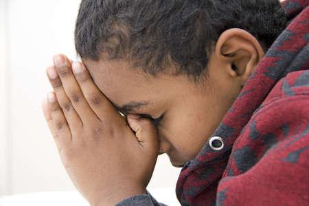 inginocchiarsi: Un giovane ragazzo durante la sua preghiera quotidiana Archivio Fotografico