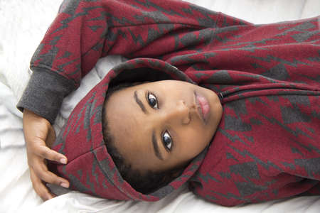 leisureliness: A young african boy resting comfortably on his bed Stock Photo