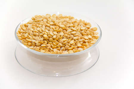 miser: Yellow split peas on a clear plate with with background