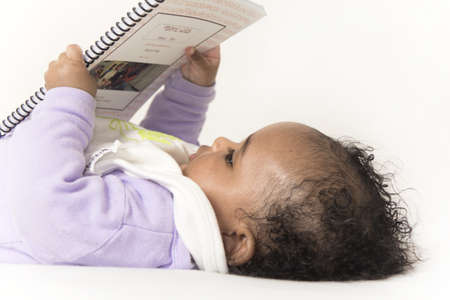 A little baby girl concentrating on a book she is holding Stock Photo - 8764347