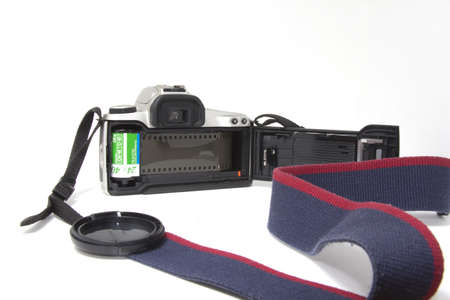 A 35mm SLR camera open from the back and showing the loaded film