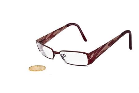 pennypinching: A  pair of eye glasses keeping a close eye on a canadian dollar bill.