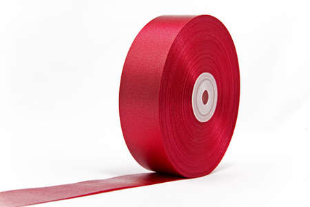 A roll of shiny red ribbon unrolled like a giant red carpet  photo