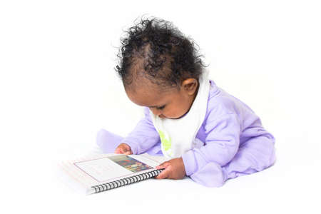 A little baby girl concentrating on a book she is holding photo