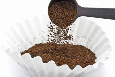プラスチック製のスクープとペーパー フィルターに挽いたコーヒーを注ぐ 写真素材