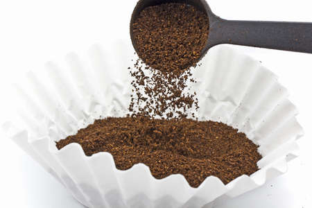 Pouring ground coffee into a paper filter with a plastic scoop Stok Fotoğraf