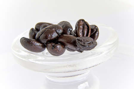 Roasted glossy coffee beans on a white background