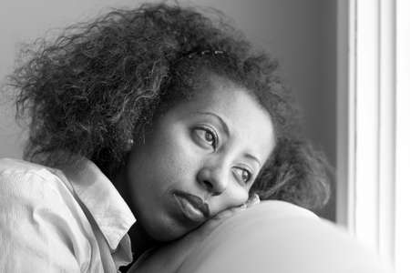Nostalgic Ethiopan woman looking out the window in deep thought photo