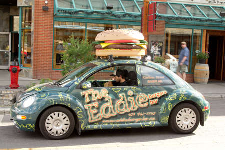 A giant burger on top of a volkswagen beetle