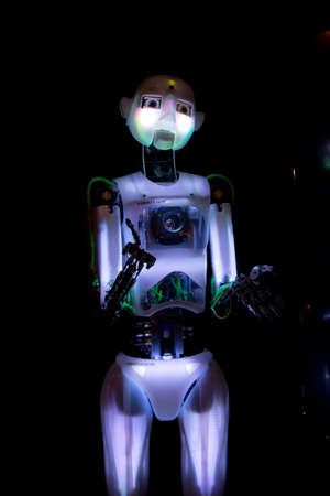 A neon colored glowing robot on display at the Telus Science musium in Edmonton stretching out its hands to the crowd