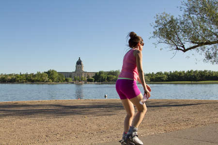 regina: A young woman rollerblading by Wascana Lake on a beautiful afternoon in Regina, Canada