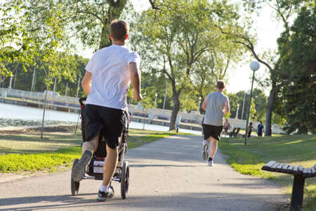 A man jogging while pushing a stroller on a beautiful sunny afternoon along side Wascana lake