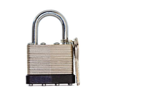 Close-up shot of a silver colored metal padlock with its key Banco de Imagens