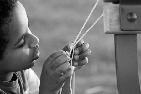 A young boy concentrating hard to untie the knows on a string