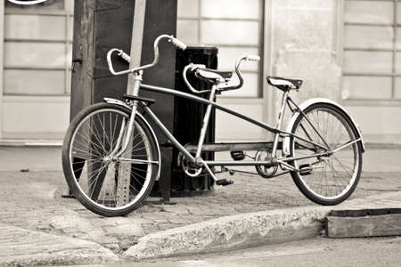 An old two seater bike parked on the streets